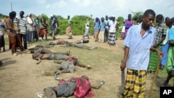 Des villageois regardent les corps de présumés assaillants, membres de la tribu Pokomo, au village de Kipao (21 déc. 2012)
