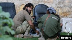 Rebel fighters of al-Jabha al-Shamiya (Levant Front) have their meal in the rebel-held al-Sheikh Said neighborhood of Aleppo, Syria, Sept.1, 2016.