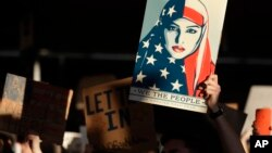 A protester holds a sign at San Francisco International Airport during a demonstration to denounce President Donald Trump's executive order that bars citizens of seven predominantly Muslim-majority countries from entering the U.S., Jan. 28, 2017.