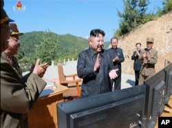 FILE - This image made from video of a news bulletin aired by North Korea's KRT July 4, 2017, shows what was said to be North Korea leader Kim Jung Un, center, applauding after the launch of a Hwasong-14 intercontinental ballistic missile, ICBM, in North Korea.