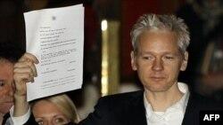 Ông Assange giơ cao hồ sơ của tòa án cho các nhà báo thấy, bên ngoài một Tòa án ở London, sau khi ông được phép tại ngoại