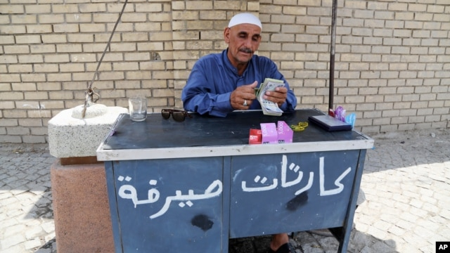 FILE - An Iraqi street currency exchanger counts banknotes in Baghdad, Aug. 8, 2015.