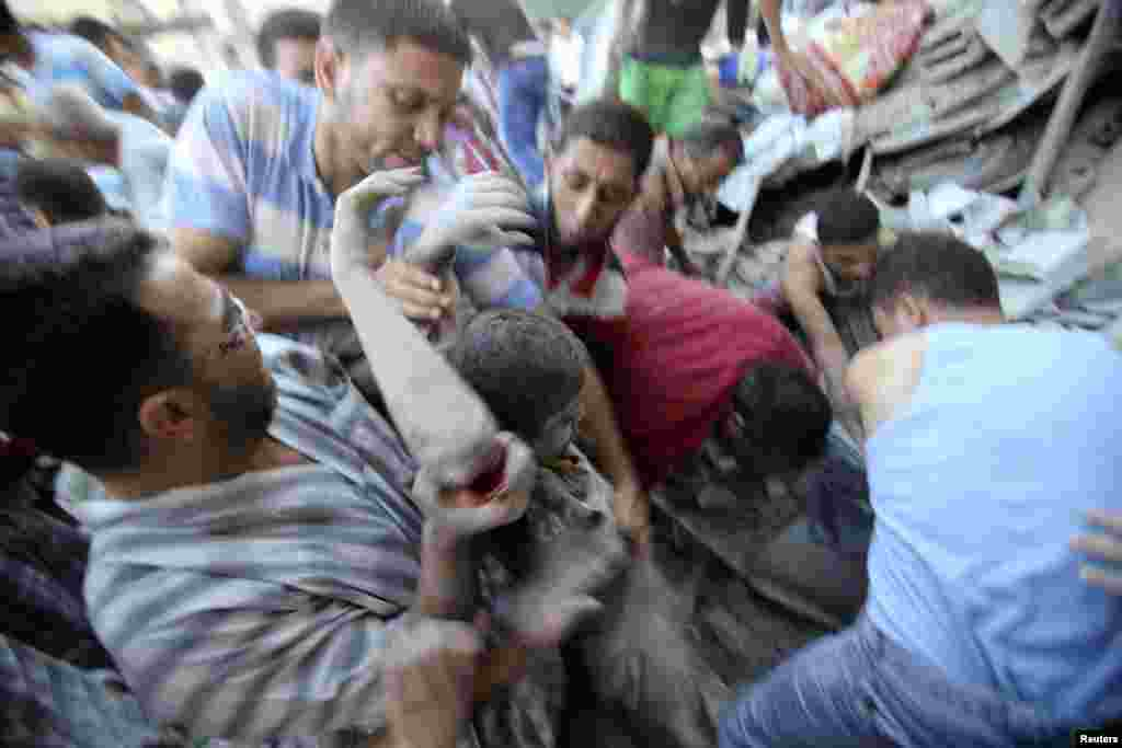 Palestinians rescue Mahmoud al-Ghol from the rubble of a house in Rafah, in the southern Gaza Strip, Aug. 3, 2014.