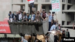 Para pendukung kelompok Syiah Houthi menaiki buldozer dalam demo di Sana'a hari Minggu (7/9).