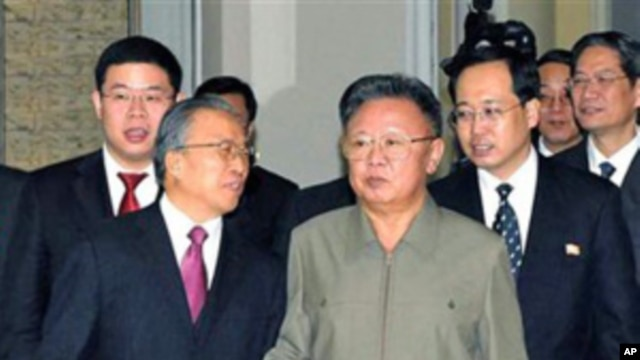 In this photo released by Korean Central News Agency via Korea News Service in Tokyo, North Korean leader Kim Jong Il, center right, and Chinese State Councilor Dai Bingguo, center left, walk together in Pyongyang, 9 Dec. 2010