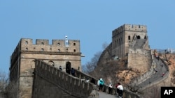 中國北京,在新型冠狀病毒爆發後重新開放的八達嶺長城上,遊客戴著防護口罩行走。