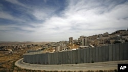 A section of the controversial Israeli barrier is seen from Jerusalem and shows the Shuafat refugee camp (R) in the West Bank near Jerusalem, and Pisgat Zeev (L) in an area Israel annexed to Jerusalem after capturing it in the 1967 Middle East war, May 25