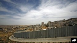A section of the controversial Israeli barrier is seen from Jerusalem and shows the Shuafat refugee camp (R) in the West Bank near Jerusalem, and Pisgat Zeev (L) in an area Israel annexed to Jerusalem after capturing it in the 1967 Middle East war (File P