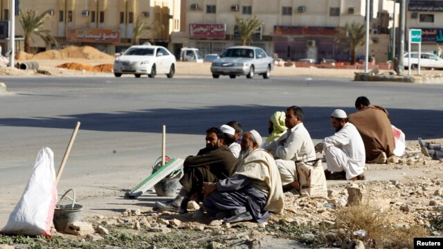 Foreign construction laborers rest on a street in Riyadh, Dec. 3, 2012.
