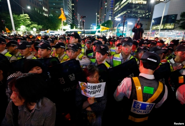 A woman holding a sign stands in front of a barricade of policemen as they march on a street after taking part in a candlelight rally to mourn victims of sunken ferry Sewol and denounce the government's handling of the disaster in central Seoul, South Kor