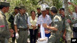 Argentine Gendarmerie members speaking with locals next to packages of cocaine in a privately owned field. Locals noticed small planes flying low over a field for no apparent reason, authorities in Argentina found some 700 kilos (1,543 lbs.) of cocaine bu
