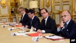 French President Francois Hollande, flanked by his Interior Minister Bernard Cazeneuve, right, and Prime Minister Manuel Valls, 2nd left, looks on during a meeting with French representatives of the different religion at the Elysee Palace in Paris, Wednes