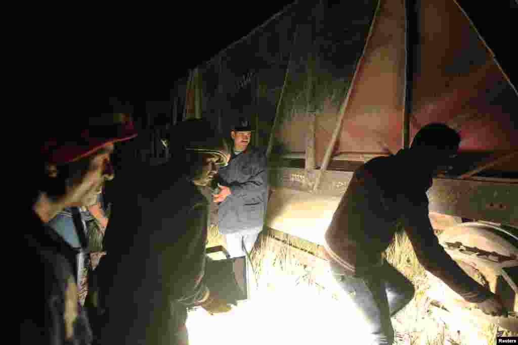 People inspect the site following a military train crash in Badrasheen, Egypt, January 15, 2013.