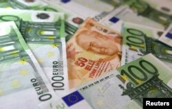 FILE - Turkish Lira and Euro banknotes are seen in this picture taken June 25, 2018. Turkey's is borrowing more than $15 billion monthly from global markets to meet its financial obligations.