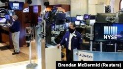 Špekulanti na berzi u Njujorku sa maskama i na socijalnoj distanci, prvog dana otvaranja podijuma za trgovinu poslije više od dva mjeseca pauze zbog COVID 19 (Foto: Reuters/Brendan McDermid)