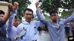 FILE - Image made from video released by the Democratic Voice of Burma, July 18, 2017, shows (L-R) Burmese journalists Lawi Weng, from the Irrawaddy, Aye Nai, from the Democratic Voice of Burma, and Pyae Bone Naing, from the Democratic Voice of Burma, raising chained wrists decrying lack of freedom and democracy, Shan state, Myanmar.