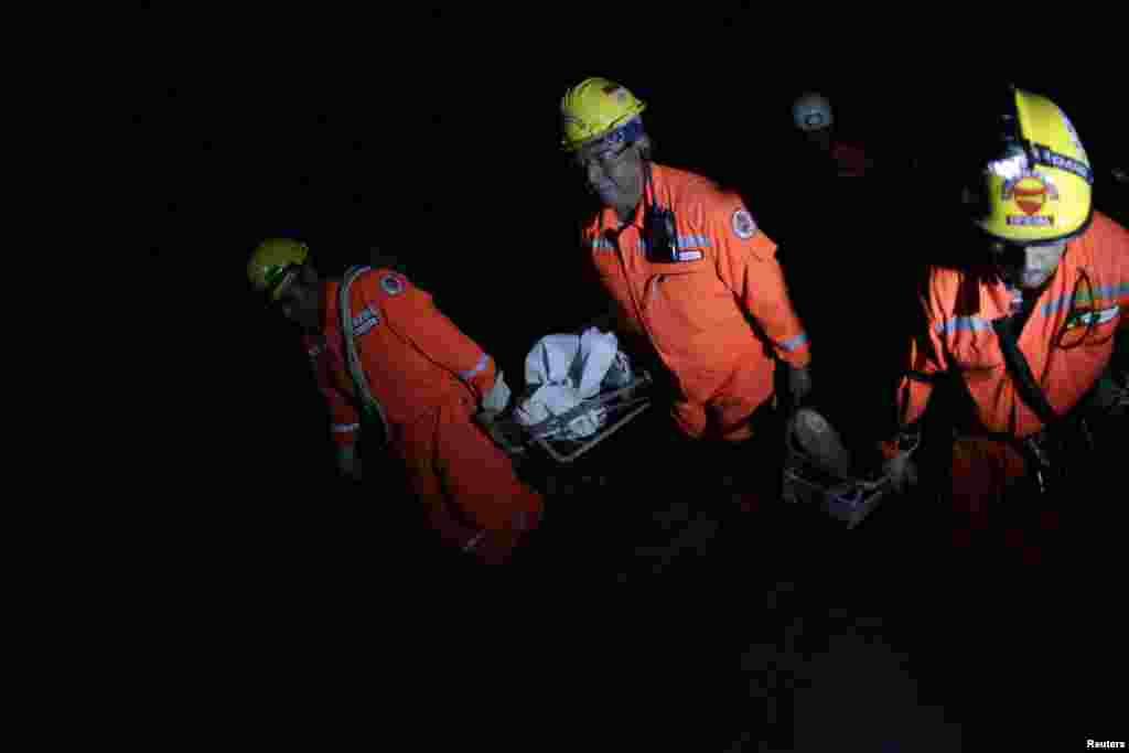 7일 강진으로 인해 사망한 희생자들의 시신을 옮기는 구조대원들.