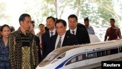 Presiden Joko Widodo (kedua dari kiri) dan Manajer Umum China Railway Corp. Sheng Guangzu (tengah) berdiri di sebelah model kereta api dalam acara peletakan batu pertama proyek kereta cepat Jakarta-Bandung di Walini, Jawa Barat, 21 Januari 2016.