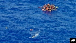 FILE - Migrants swim while others climbed onto a rescue dinghy to wait for rescuers on the scene of the capsizing and sinking of a fishing boat in the Mediterranean sea off Libya.