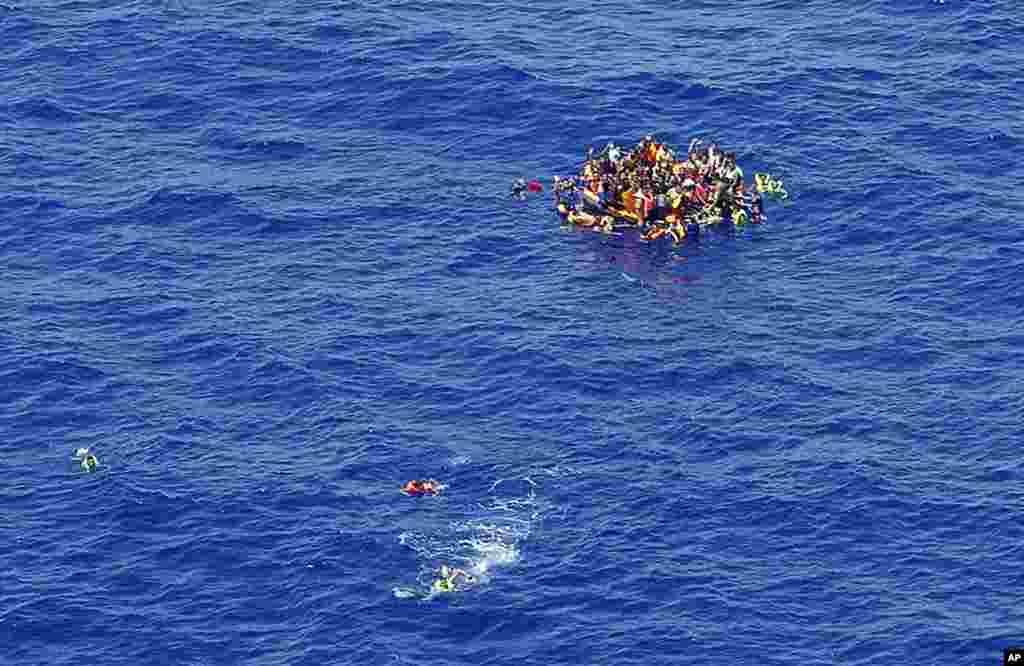 Migrants swim while others climb onto a rescue dinghy, waiting for rescuers on the scene of the capsizing and sinking of a fishing boat in the Mediterranean sea off Libya. The Italian coast guard and Irish navy said at least 367 people were saved, although 25 bodies also were found. Many other are feared to have died during the capsizing of the fishing boat in the latest human smuggling tragedy. (Credit: Italian Navy)