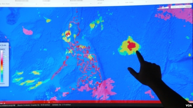 Project NOAH Executive Director Mahar Lagmay points at a satellite image of a tropical depression approaching the Philippines at the National Institute of Geological Sciences, University of the Philippines Diliman campus, Sept. 20, 2012. (VOA/Simone Orendain)