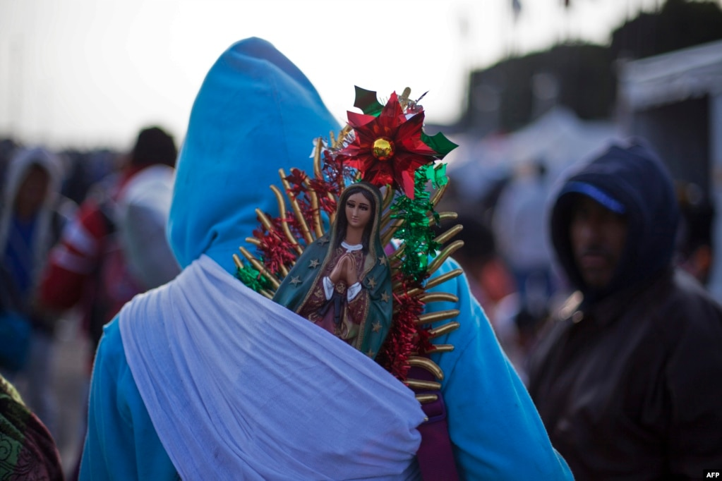 A pilgrim carries a small statue of the Virgin of Guadalupe on his back during the yearly celebrations at the Basilica of Guadalupe in Mexico City.