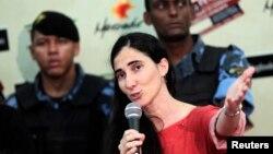 Custodiada por guardias de seguridad, Yoani da una rueda de prensa entre admiradores suyos y simpatizantes del régimen cubano.