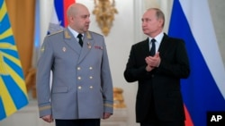 FILE - Russian President Vladimir Putin applauds Col. Gen. Sergei Surovikin during an awards ceremony for troops who fought in Syria, in the Kremlin, in Moscow, Dec. 28, 2017. Putin says Russia's action in Syria has demonstrated the power of the nation's modernized military to the world.