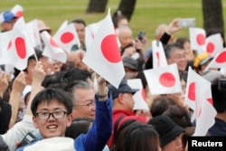Warga melambaikan bendera Jepang saat menunggu Kaisar Naruhito di luar Istana Kekaisaran di Tokyo, Jepang, 1 Mei 2019.