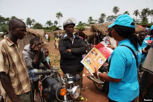 A UNICEF worker talks with motorcycle taxi drivers about Ebola and precautions in Voinjama, Liberia, in this UNICEF handout photo.