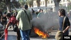 Para mahasiswa Italia bentrok dengan polisi dalam protes yang disertai kerusuhan di Palermo, Sisilia, Rabu.