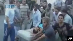 REUTERS CANNOT INDEPENDENTLY VERIFY CONTENT OF THE VIDEO FROM WHICH THIS STILL IMAGE WAS TAKEN. A man on a stretcher is carried to Al Badra Hospital in Hama in this still image taken from video July 31, 2011