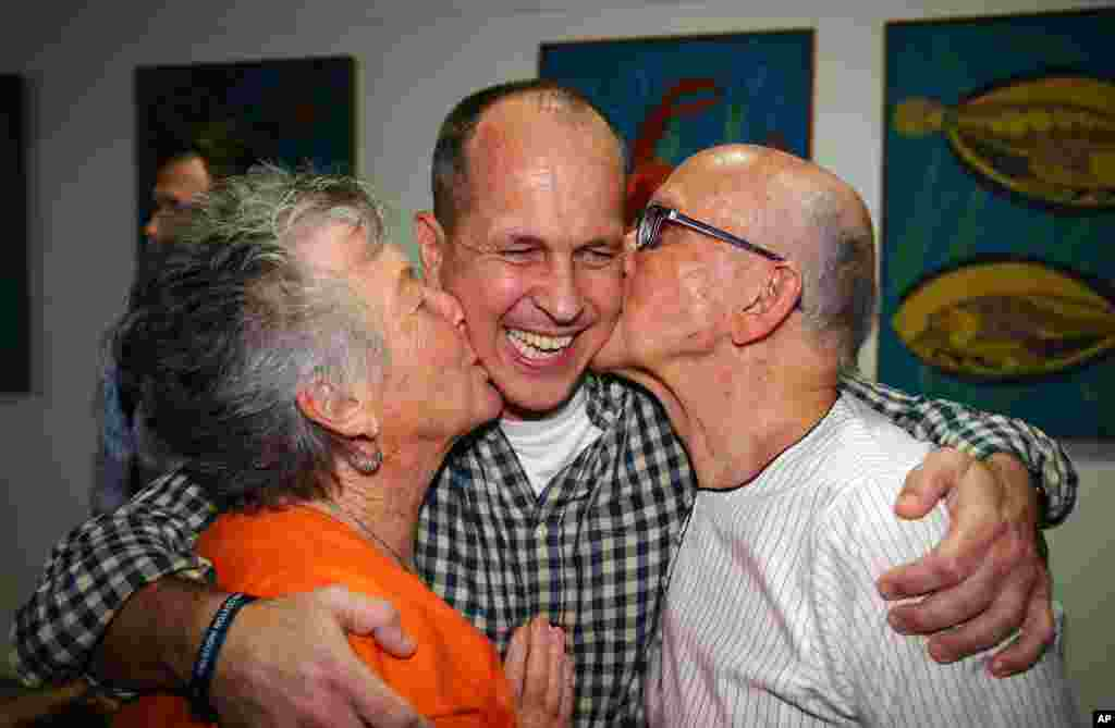 Australian journalist Peter Greste is hugged by his mother Lois, left, and father Juris, right, after his arrival in Brisbane, Australia. Greste, a reporter for Al-Jazeera ,was released from an Egyptian prison and deported after more than a year behind bars.
