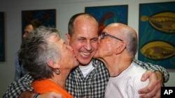 Australian journalist Peter Greste is hugged by his mother Lois, left, and father Juris, right, after his arrival in Brisbane, Australia, Thursday, Feb. 5, 2015.
