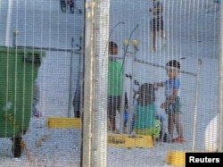 FILE - An undated photo by Amnesty International purports to show children playing near a fence at an Australian-run detention center on the Pacific island of Nauru.