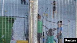 FILE - An undated image provided by Amnesty International purportedly shows children playing near a fence at an Australian-run detention center in the Pacific island nation of Nauru.