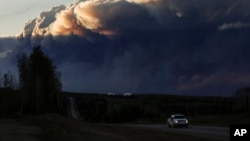 Smoke billows from the Fort McMurray wildfires as a truck drives down the highway in Kinosis, Alberta.