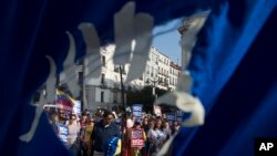 Seen through a hole in a torn Venezuelan flag, people gather to protest in support of families and friends in Venezuela during a protest in Madrid, Spain, April 19, 2017. Opponents of Venezuelan President Nicolas Maduro called on people to take to the streets and march against the embattled socialist leader.