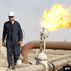 A worker walks on oil pipe at West Qurna oilfield in Iraq's southern province of Basra November 28, 2010. U.S. oil major ExxonMobil and its partners have awarded a contract to oil services firm Schlumberger Ltd to drill 10 wells in Iraq's West Qurna Phase