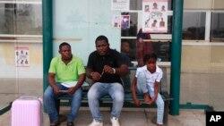 Hành khách ngồi dưới tấm bảng cảnh báo vi rút Ebola tại sàn bay quốc tế ở Malabo, Guinea Xích Đạo, 16/1/15