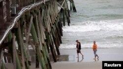 Khách du lịch đi bộ trên bãi biển Surfside, bang South Carolina trước khi bão tới, ngày 3/7/2014.