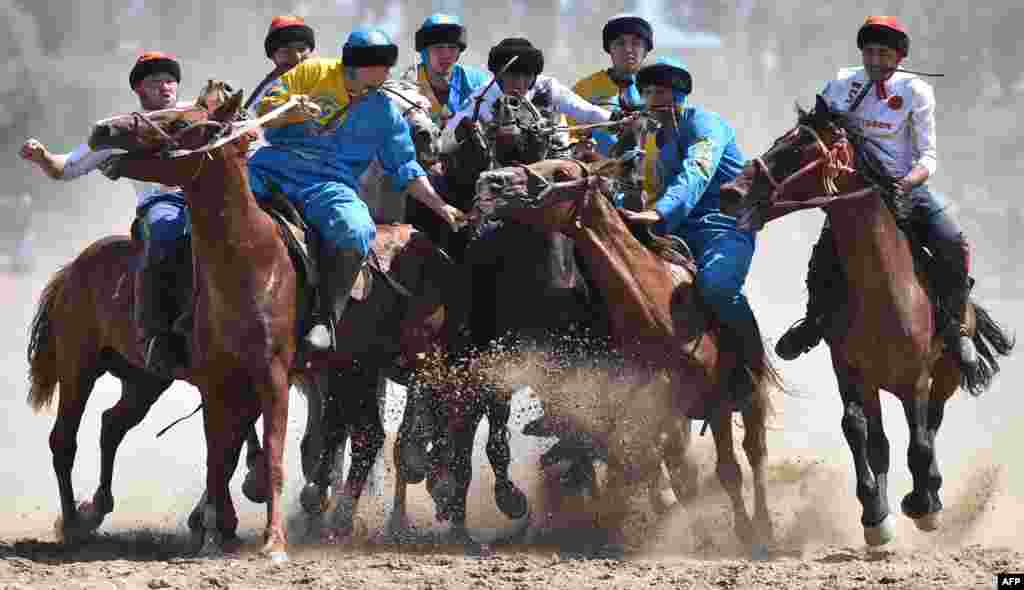 Russian (white) and Kazakh (blue) riders play the traditional Central Asian sport Buzkashi also known as Kok-Boru or Oglak Tartis during the World Nomad Games 2018 in Cholpon-Ata, eastern Kirghizstan.