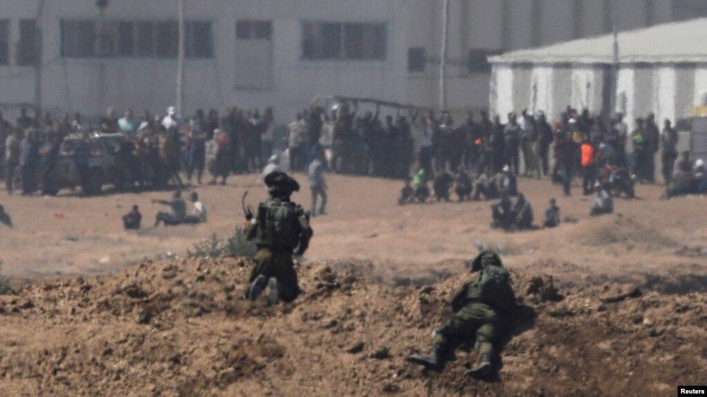 以色列士兵在加沙地帶的以色列一邊注視著巴勒斯坦抗議者。(2018年5月14日)