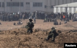 Israeli soldiers, on the Israeli side of the border with the Gaza Strip, watch Palestinian protesters, in Gaza, May 14, 2018.