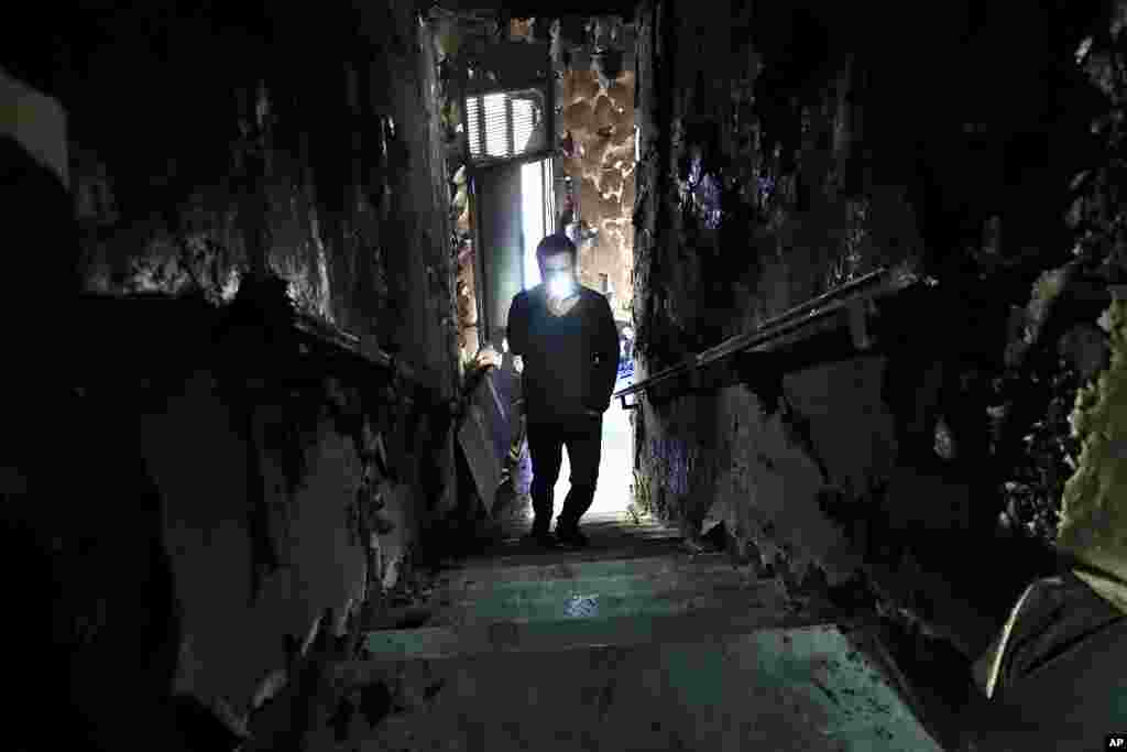 A man lights his mobile phone as he films the burned stairs of Tripoli municipality that was set on fire by protesters during a protest against deteriorating living conditions and strict coronavirus lockdown measures, in Tripoli, Lebanon.