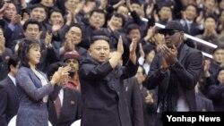 북한의 김정은 국방위원회 제1위원장이 28일 평양에서 열린 미국의 묘기 농구단 시범 경기장에 참석, 방북 중인 전 미국프로농구(NBA) 선수 데니스 로드먼과 함께 관중들에게 인사하고 있다. 왼쪽은 부인 리설주.