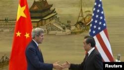 ລມຕ ຕ່າງປະເທດສະຫະລັດ ທ່ານ John Kerry (ຊ້າຍ) ແລະ ລມຕ ຕ່າງປງະເທດຈີນ ທ່ານ Wang Yi ຈັບມືກັນ ຫຼັງຈາກ ກອງປະຊຸມຖະແຫຼງຂ່າວ ທີ່ກະຊວງຕ່າງປະເທດຈີນ ຢູ່ປັກກິ່ງ (16 ພຶດສະພາ 2015)