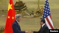 美国国务卿克里(左)与中国外长王毅2015年5月16日在北京中国外交部举行联合记者会后握手。