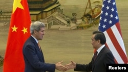 U.S. Secretary of State John Kerry, left, and Chinese Foreign Minister Wang Yi shake hands after a news conference following meetings at the Ministry of Foreign Affairs in Beijing, May 16, 2015.