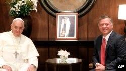 Raja Abdullah dari Yordania (kanan) menyambut Paus Fransiskus di Istana Kerajaan Yordania di Amman (24/5).